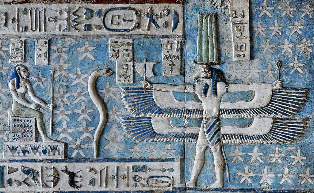 """[EGYPT 29550]'Good wind from the South at Dendera.' Representing the south wind, a ram-headed creature with double outstretched wings, holding a little sail and the 'ankh' sign of life, can be found on the astronomical ceiling in the outer hypostyle hall of the Hathor Temple at Dendera.The ceiling consists of seven separate strips but here we are looking at the southern end of the upper register of the SECOND STRIP EAST from centre.A caption near the head of the wind figure proclaims him to be """"the good wind from the south"""". Wind creatures such as these only appear in Egyptian monuments of the Greek-Roman period.The lion-headed goddess and the snake are decans.Decans were essentially 36 stars or star groups near the ecliptic  whose rise or transit could be used to tell the time during the night. Eventually they were also used by astronomers as place-markers in the sky to divide up the Ecliptic in equal portions. Decans first appear during the Middle Kingdom on the inside of coffin lids, providing the deceased with his own private start clock. Unfortunately, during the subsequent centuries many different lists of decanal stars were developed and very few of these stars can be identified on a modern star map.The decans in this register were listed by Neugebauer and Parker as belonging to the Seti I B decan family. A peculiarity of these decans is that each is associated with a certain mineral, metal or type of wood. It is mentioned in a little caption near each figure. Thus the seated lion-headed goddess (decan no. 22) is associated with carnelian and gold, while the erect white serpent (no. 21) is coupled with dark flint and gold.For an overview of this ceiling strip see picture 29539.This part of the Dendera Temple was built during theRoman period (first century AD). Photo Paul Smit."""