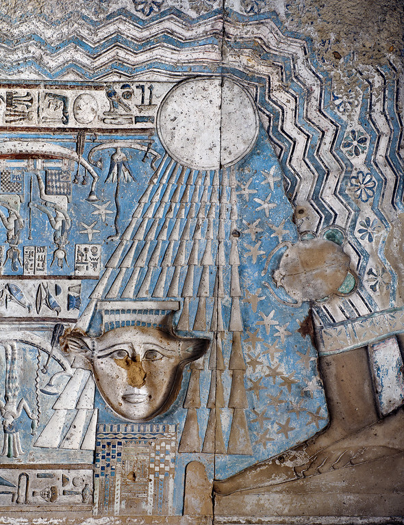 [EGYPT 29528]'Birth of the sun in Hathor Temple at Dendera.' The rising sun is born from the lap of sky goddess Nut on the astronomical ceiling in the outer hypostyle hall of the Hathor Temple at Dendera. The ceiling consists of seven separate strips but here we are looking at a detail of the EASTERNMOST STRIP. The entire strip is enveloped by the outstretched body of the sky goddess Nut and her feet are visible in the right lower corner of this picture. The wave pattern on Nut's dress symbolizes the cosmic river on which the sun traveled during the night. The rays of the rising sun touch the head of the goddess Hathor which is located on top of a simplified image of a temple. The scene portrays the first day of the Egyptian New Year on which a statue of Hathor, brought from a crypt in the temple and placed on its roof, was rejuvenated by the first rays of the New Year sun. A similar scene can be found on the ceiling of the Wabet (see picture 29610). To the right of the sun rays we see Cancer, one of the six zodiac  signs that are represented in this ceiling strip. These signs are of Babylonic-Greek origin and are not found in Egypt before it was conquered by Alexander the Great in 332 BC.To the left of the sun we see (upside down) a small boat carrying a lotus flower from which emerges a snake. The snake is a symbol for the rising sun on the first day of the New Year, the lotus flower being the first object that appeared on the primordial sea on the first day of the world creation. It is similar to the famous image of the sun-snake in a cosmos-bulb which is found in the southern crypt of the temple (see pictures 29604-607).For an overview of this ceiling strip see picture 29526.This part of the Dendera Temple was built during the Roman period (first century AD). Photo Mick Palarczyk.