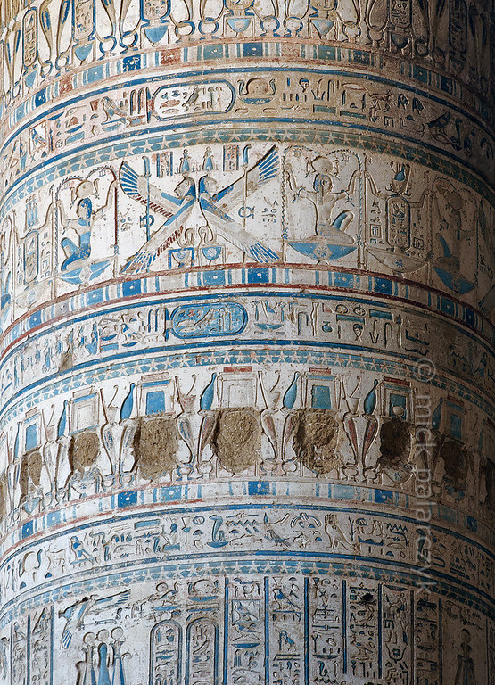 [EGYPT 29519]'Column in Hathor Temple at Dendera.' The shafts of the columns in the outer hypostyle hall (or pronaos) of the Hathor Temple at Dendera are covered with intricate decorations. One of the more conspicuous figures is Heh, the god of eternity, depicted in a crouching position. He is holding a (leafless) palm stem in each hand, which symbolized long life to the Egyptians, the years being represented by the notches on the stem. The winged lion-headed serpents are personifications of the cobra goddess Wadjet.Sadly, a row of Hathor heads has been defaced.This part of the Dendera Temple was built during the Roman period (first century AD). Photo Mick Palarczyk.