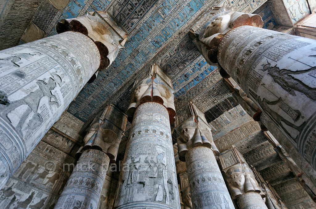"""[EGYPT 29524]'Outer hypostyle hall of Hathor Temple at Dendera.' The columns in the outer hypostyle hall (or pronaos) of the Hathor Temple at Dendera are crowned by four-sided capitals carved with the face of the cow-eared goddess. The faces symbolize the four cardinal points of the universe and stress the universal character of the sky goddess Hathor, who was also called """"Lady with the four Faces""""The ceiling has recently been cleaned of soot and dust and is decorated with a complex set of astronomical figures, constellations, planets and a zodiac.This part of the Dendera Temple was built during the Roman period (first century AD). Photo Mick Palarczyk."""