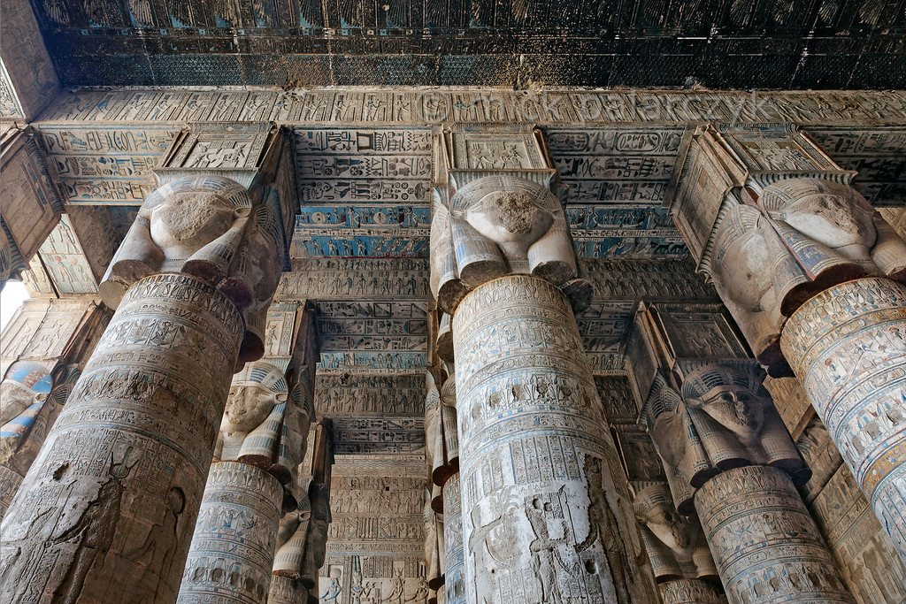 """[EGYPT 29523]'Outer hypostyle hall of Hathor Temple at Dendera.' The columns in the outer hypostyle hall (or pronaos) of the Hathor Temple at Dendera are crowned by four-sided capitals carved with the face of the cow-eared goddess. The faces symbolize the four cardinal points of the universe and stress the universal character of the sky goddess Hathor, who was also called """"Lady with the four Faces"""".Here we are looking towards the eastern end of the hall.The ceiling has recently been cleaned of soot and dust and is decorated with a complex set of astronomical figures, constellations, planets and a zodiac. One strip has been left uncleaned however and this is visible as a black zone at the upper edge of the picture.This part of the Dendera Temple was built during the Roman period (first century AD). Photo Mick Palarczyk."""