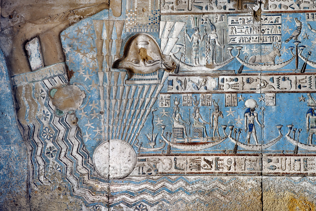 [EGYPT 29527]'Birth of the sun in Hathor Temple at Dendera.' The rising sun is born from the lap of sky goddess Nut on the astronomical ceiling in the outer hypostyle hall of the Hathor Temple at Dendera. The ceiling consists of seven separate strips but here we are looking at a detail of the EASTERNMOST STRIP. The entire strip is enveloped by the outstretched body of the sky goddess Nut and her feet are visible in the left upper corner of this picture. The wave pattern on Nut's dress symbolizes the cosmic river on which the sun traveled during the night. The rays of the rising sun touch the head of the goddess Hathor which is located on top of a simplified image of a temple (seen upside down here). The scene portrays the first day of the Egyptian New Year on which a statue of Hathor, brought from a crypt in the temple and placed on its roof, was rejuvenated by the first rays of the New Year sun. To the left of the sun rays we see Cancer, one of the six zodiac  signs that are represented in this ceiling strip. These signs are of Babylonic-Greek origin and are not found in Egypt before it was conquered by Alexander the Great in 332 BCOn the right we see the end of the two registers which make up the rest of this strip. The upper register starts with a boat carrying the standing goddesses Anukis and Satis, who represent a constellation south of the Ecliptic (the astronomical location is known from the famous round zodiac of Dendera in the Louvre). Anukis, as personification of the Nile, is pouring water from two vessels. Satis, another water goddess, is wearing the crown of upper Egypt. This watery constellation is closely associated with the next heavenly body: Sothis (the star Sirius) depicted as a cow on a boat. The rise of Sirius on the eastern horizon, after a few weeks of invisibility, signaled the beginning of the summer Nile flood for the Egyptians and the beginning of the New Year.Next comes a constellation or star which is called 'Horus-who-is-on-his-pillar'