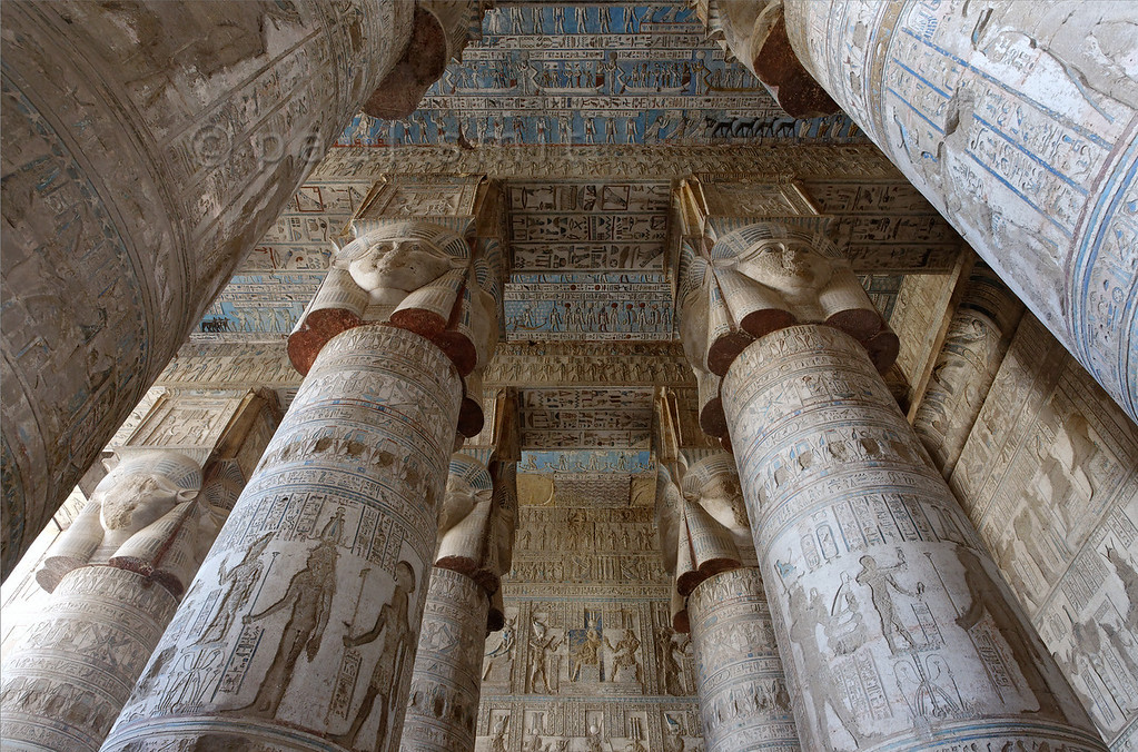 """[EGYPT 29521]'Outer hypostyle hall of Hathor Temple at Dendera.' The columns in the outer hypostyle hall (or pronaos) of the Hathor Temple at Dendera are crowned by four-sided capitals carved with the face of the cow-eared goddess. The faces symbolize the four cardinal points of the universe and stress the universal character of the sky goddess Hathor, who was also called """"Lady with the four Faces"""".Here we are looking towards the eastern end of the hall.The ceiling has recently been cleaned of soot and dust and is decorated with a complex set of astronomical figures, constellations, planets and a zodiac.This part of the Dendera Temple was built during the Roman period (first century AD). Photo Paul Smit."""