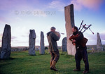 [BRITAIN.HEBRIDES 27671] ?Piping at Callanish stone circle .?  On a windy evening local musicians are enhancing the mystic atmosphere of the neolithic stone circle at Callanish on th ...